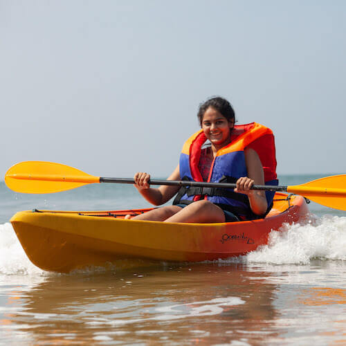 Girl having fun on the beach on an ocean tour activity in a rent kayak at Arambol Goa