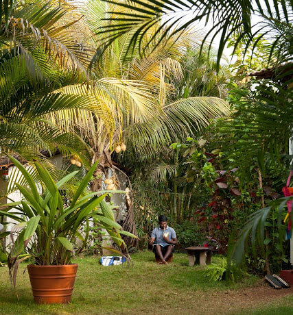 Surfer chilling with his surf board in our beautiful garden at the Surf Wala guest house hotel