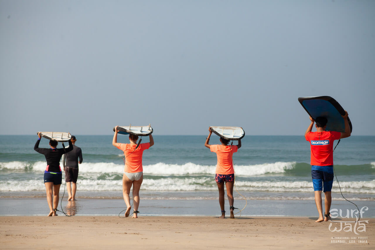 A group of guys and girls carrying surf boards head to the water to start surfing with their instructor leading the way